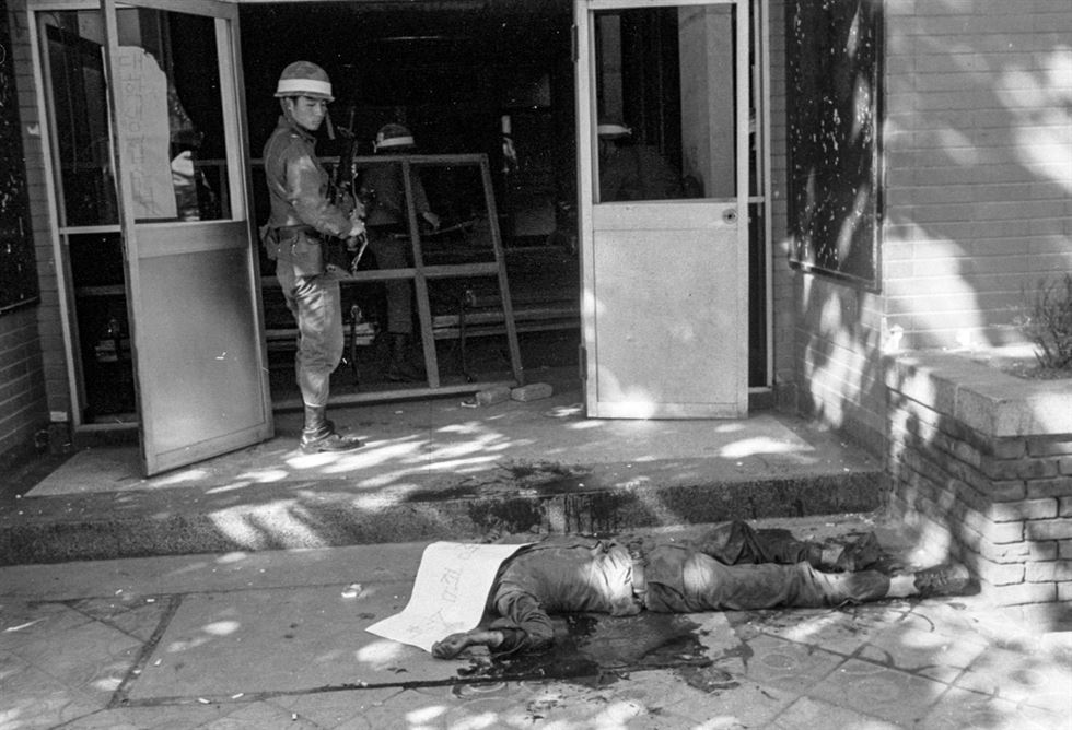 A woman passes a young man who fell on Geumnam Street, Gwangju, on May 20, 1980. Two fully armed soldiers stand guard nearby. / Korea Times