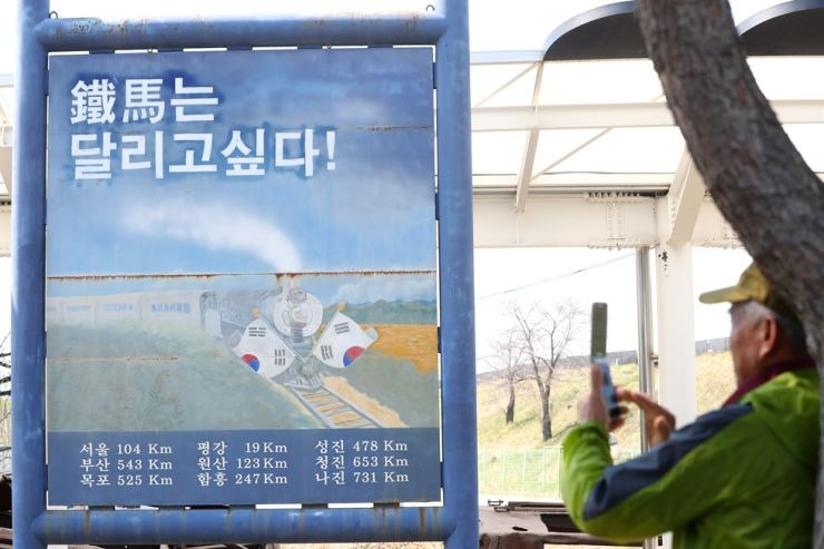 A tourist takes a photo of a sign at Woljeong-ri Station inside the Demilitarized Zone in Cheorwon County, Gangwon Province on April 25, 2018. The station was closed during the Korean War. / Yonhap