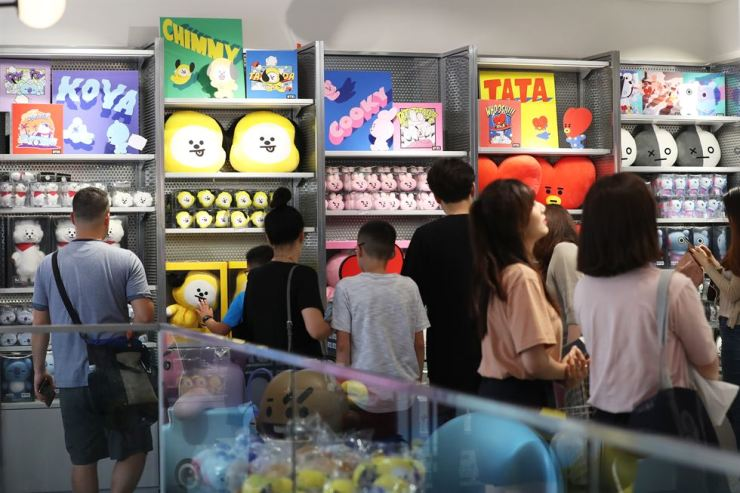 People buy BTS merchandise at a Line Friends store in Mapo-gu, Seoul, Wednesday. Retailers have been enjoying brisk sales of the merchandise as well as the album packages with the group's increasing popularity worldwide. / Yonhap