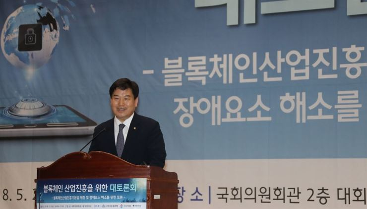 Rep. Hong Eui-rak of the ruling Democratic Party of Korea speaks during a forum on cryptocurrencies and blockchain technology at the National Assembly in Seoul, Wednesday. He said a bill aimed at allowing the launch of new cryptocurrencies here is in the making. / Yonhap