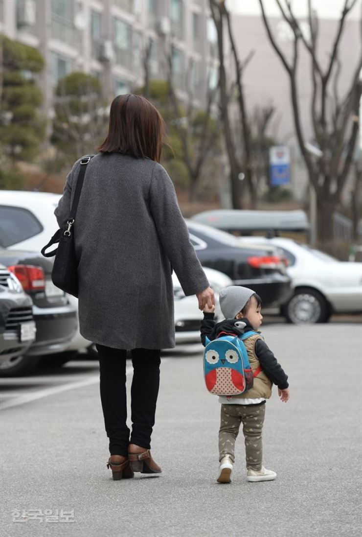 A working mom takes her child to a daycare center. Korea has been ranked at the bottom in the glass ceiling index, with many women giving up their careers due to the tough working environment. / Korea Times photo by Shin Sang-soon