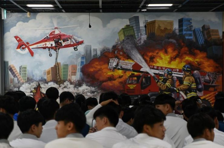 Students assemble in the lobby of Gwangnaru Safety Experience Center, in front of a very violent mural fit for a PG-13 movie. / Image by Jon Dunbar