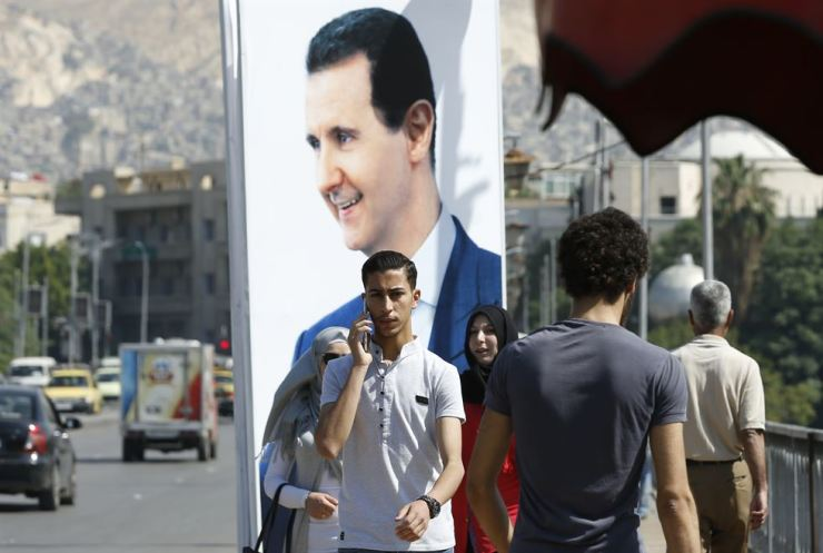 People walk near a portrait of Syrian President Bashar al-Assad hanging in a street in the Syrian capital Damascus on May 31. / AFP-Yonhap