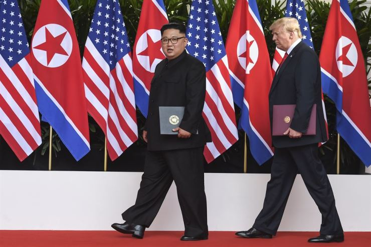 North Korean leader Kim Jong-un leads U.S. President Donald Trump after signing their joint declaration at their June 12 summit in Singapore, Tuesday. Yonhap