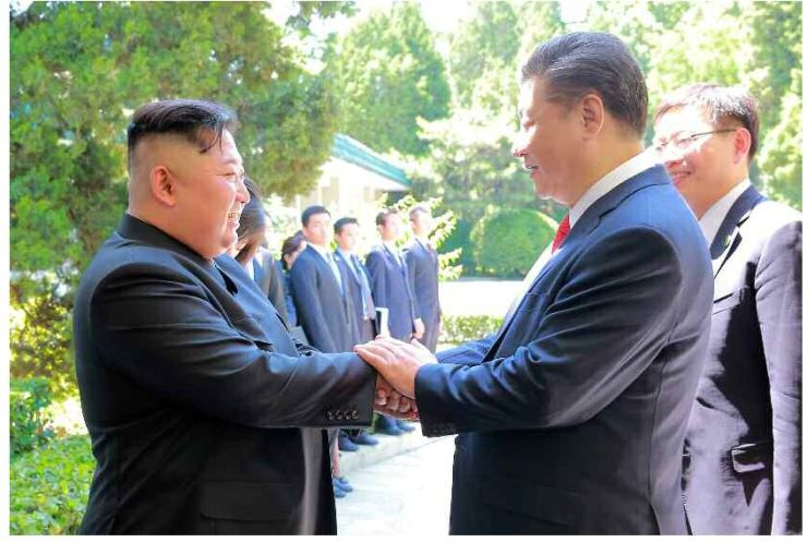 North Korean leader Kim Jong-un shakes hands with Chinese President Xi Jinping before a meeting at the Diaoyutai State Guesthouse in Beijing on Wednesday. Kim made a two-day trip to Beijing to discuss the current state of affairs with the Chinese leader and to seek cooperation in North Korea's denuclearization process. / Yonhap