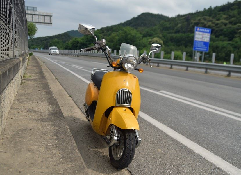 The new scooter stands in front of a cliff in Mungyeong. / Image by Jon Dunbar