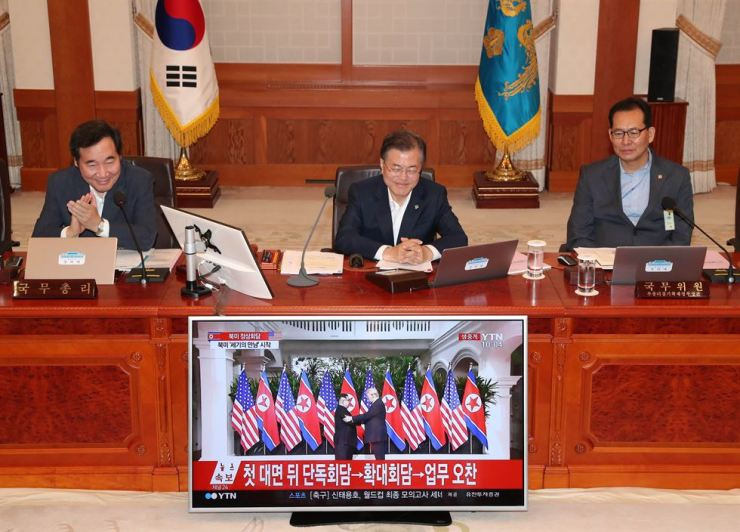 President Moon Jae-in watches the live broadcast of the June 12 U.S.-North Korea summit in Singapore during his meeting with aides at Cheong Wa Dae. Korea Times file