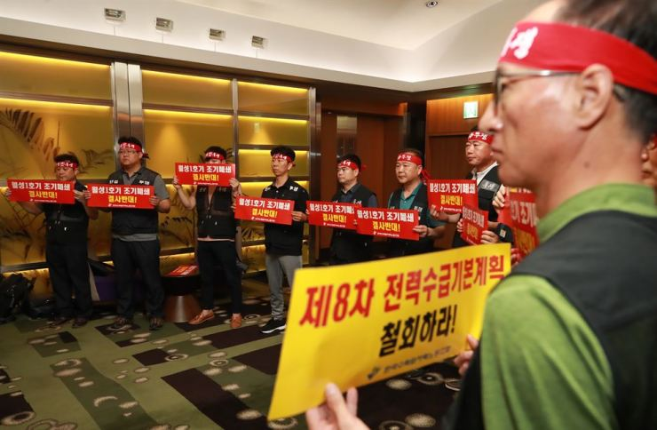 Union members of the Korea Hydro & Nuclear Power hold signs in Seoul, Friday, in a protest opposing the shutdown of the Wolsong-1 nuclear reactor. / Yonhap