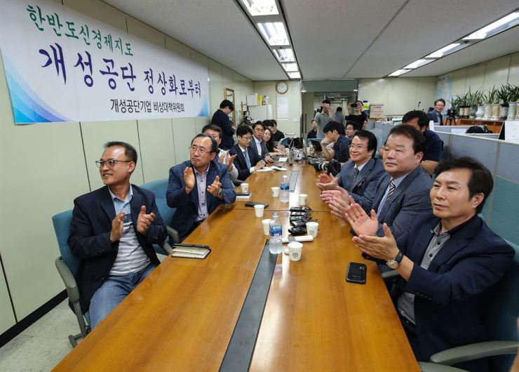 Businessmen who have factories in Gaeseong Industrial Complex clap their hands as they watch the historic summit between North Korea and the United States on TV at Korea Federation of SMEs headquarters in Seoul, Tuesday. / Yonhap