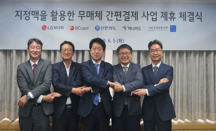 Representatives of Shinhan, BC, and Hana Card and their counterparts from IT platform service providers, LG-Hitachi and NICE Information & Telecommunication, hold hands after signing a memorandum of understanding at the LG-Hitachi headquarters in Mapo, northwestern Seoul, on Tuesday. / Courtesy of Shinhan Card