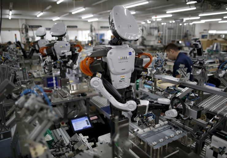 Humanoid robots work side by side with employees on an assembly line at a factory in Japan. Reuters