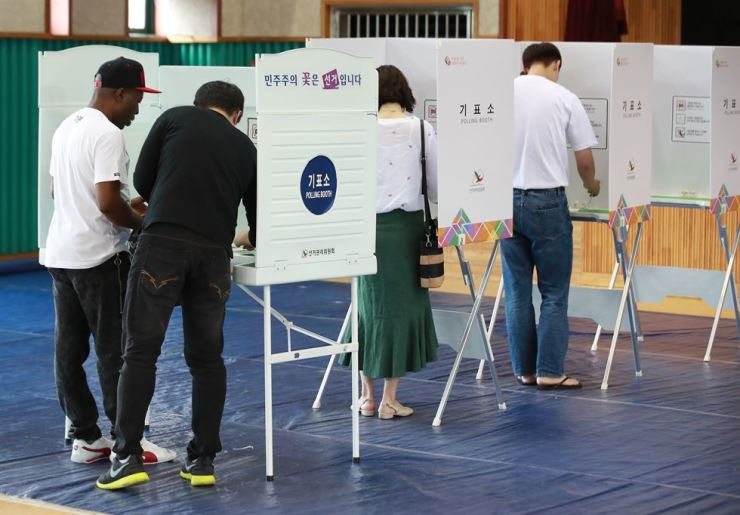 Voters cast their ballots for local elections at Itaewon Elementary School in Seoul on June 13. Yonhap