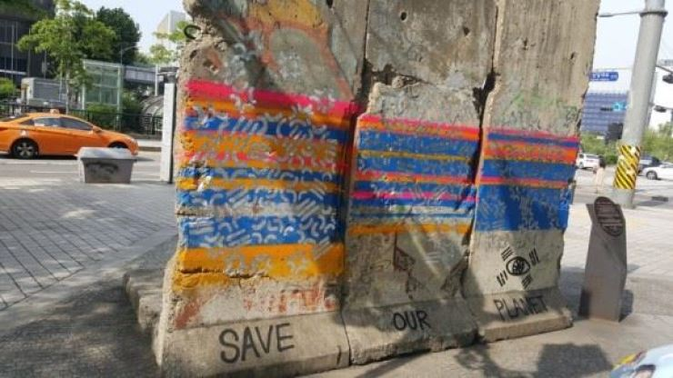 A section of the Berlin Wall displayed next to Cheonggye Stream is covered with graffiti. / Yonhap