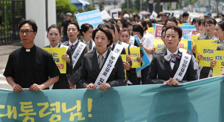 Fired KTX train attendants march from Seoul Station to Cheong Wa Dae, Monday, demanding their reinstatement and calling on President Moon Jae-in to resolve their management-labor problem. / Yonhap