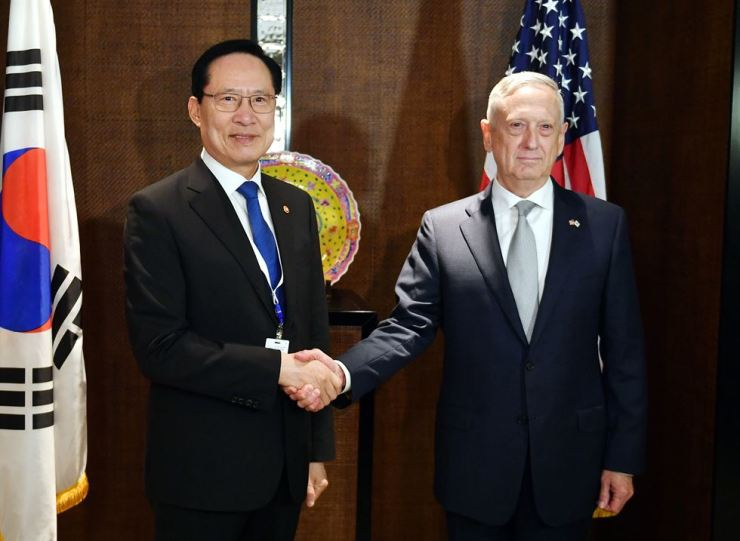 South Korean Defense Minister Song Young-moo, left, shakes hands with U.S. Secretary of Defense James Mattis ahead of their meeting on the sidelines of the Shangri-La Dialogue in Singapore, Saturday. / Yonhap