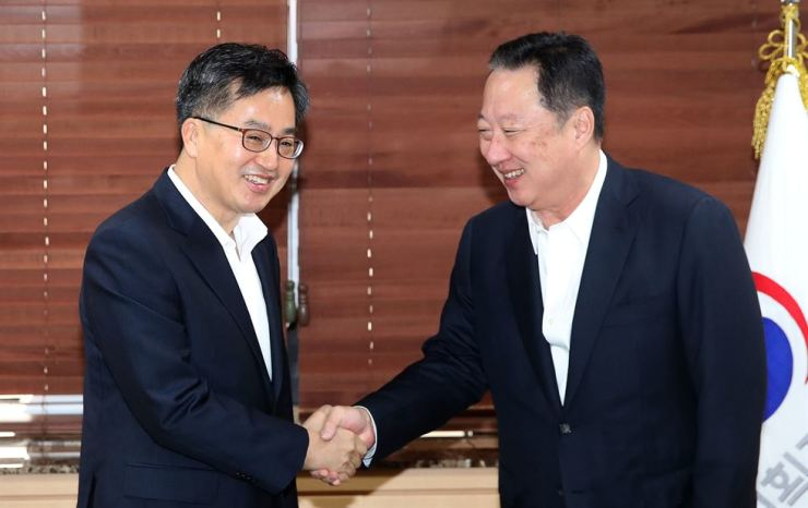 Strategy and Finance Minister Kim Dong-yeon, left, shakes hands with Korea Chamber of Commerce and Industry (KCCI) Chairman Park Yong-maan at a meeting on deregulation held in downtown Seoul, Friday. / Korea Times photo by Seo Jae-hoon