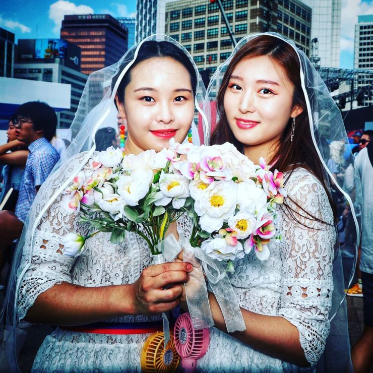 Two young bisexual women dressed up to make a point about the purest kind of matrimony at the 2018 Queer Culture Festival and parade last Saturday. They wanted to show their support for same-sex marriage in Korea. Photos by Michael Hurt