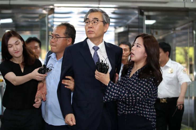 Former Fair Trade Commission Chairman Jeong Jae-chan, center, refuses to speak to reporters while entering Seoul Central District Court for questioning, Monday. / Yonhap
