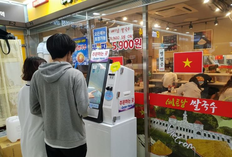 Customers place their order at an electronic kiosk in front of a Vietnamese pho restaurant inside Gangnam Station, Seoul, Thursday. / Korea Times photo by Lee Suh-yoon