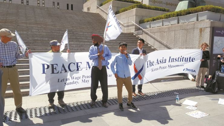 Asia Institute President Emanuel Pastreich, left, and Korea Peace Movement director Lakhvinder Singh, third from left, appear at a Peace March on May 14, 2017. / Courtesy of Asia Institute