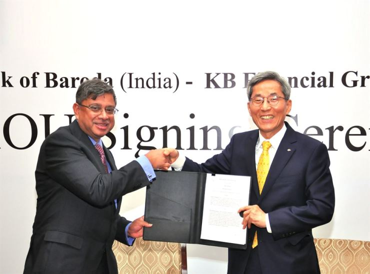 KB Financial Group Chairman Yoon Jong-kyu, right, shakes hands with Bank of Baroda CEO Shri P.S. Jayakumar during an MOU signing ceremony at Bank of Baroda head office in New Delhi, India, Tuesday. / Courtesy of KB Financial Group