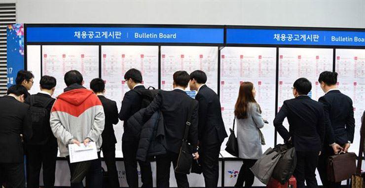 Young job seekers looking at job postings on the bulletin board. Hankookilbo