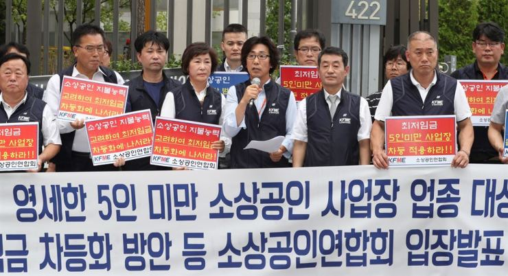 Members of the Korea Federation of Micro Enterprise hold a press conference in front of the Ministry of Employment and Labor building at the Sejong government complex, Tuesday. / Yonhap