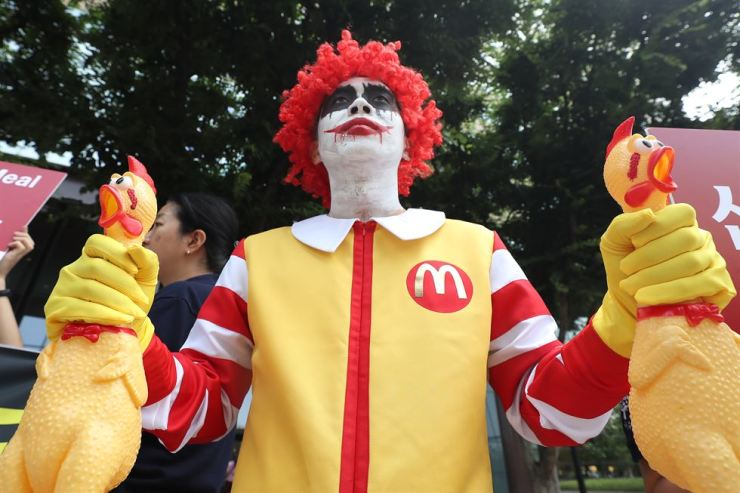 A Korean Animal Welfare Association member stages a performance in front of the McDonald's Korea headquarters in Seoul July 20 urging the company to switch to cage-free eggs as soon as possible. / Yonhap