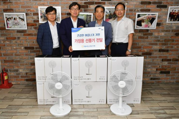 NongHyup (NH) Bank CEO Lee Dae-hoon, second from left, poses with employees and an official from a welfare center in Yongsan, Seoul, Monday, after donating 200 electric fans for elderly people living alone. NH Bank has also opened shelters at its branches for the underprivileged amid the ongoing heat wave. Courtesy of NH Bank