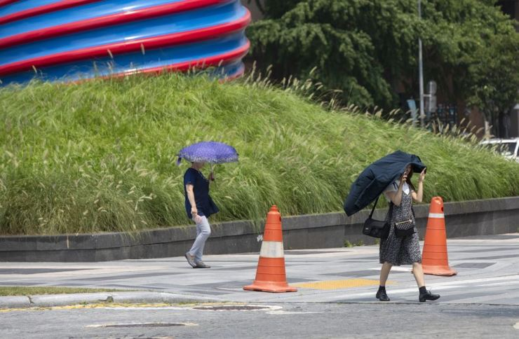 A woman uses clothing to shield herself from the sun as she crosses the street near Cheonggye Stream in central Seoul, Tuesday, amid the continuing heat wave. / Korea Times photo by Shim Hyun-chul