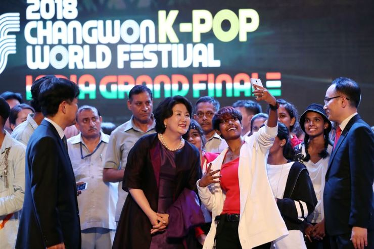 Korea's first lady Kim Jung-sook, center, poses for a selfie with a participant of the annual K-pop contest 'Changwon K-pop World Festival' held in the Siri Fort Auditorium in New Delhi, Tuesday. Kim is accompanying Korean President Moon Jae-in on his four-day state visit to India from Sunday. / Yonhap