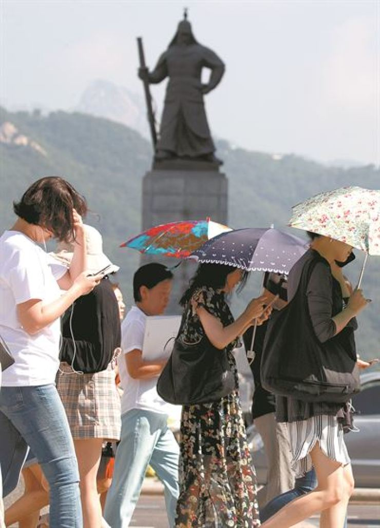 People in downtown Seoul use parasols Tuesday to avoid the scorching heat at the temperature in Seoul peaked at 34 degrees Celsius. / Yonhap