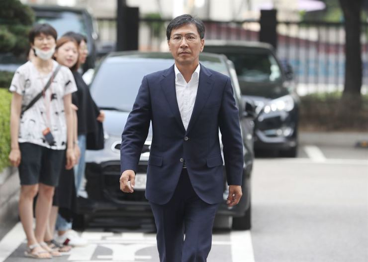 An Hee-jung, former governor of South Chungcheong Province, enters the Seoul Western District Court for a hearing on rape charges filed by his former secretary, Friday, as women's rights activists chant 'Send the offender to jail, and victim back to her life' behind him. / Yonhap