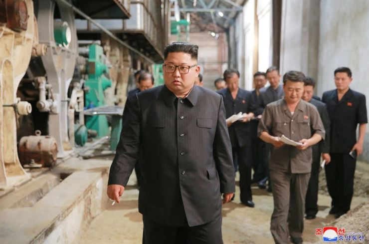 North Korean leader Kim Jong-un looks around a chemical fiber factory in the northwestern city of Sinuiju in this photo released by the Korean Central News Agency, Monday. / Yonhap