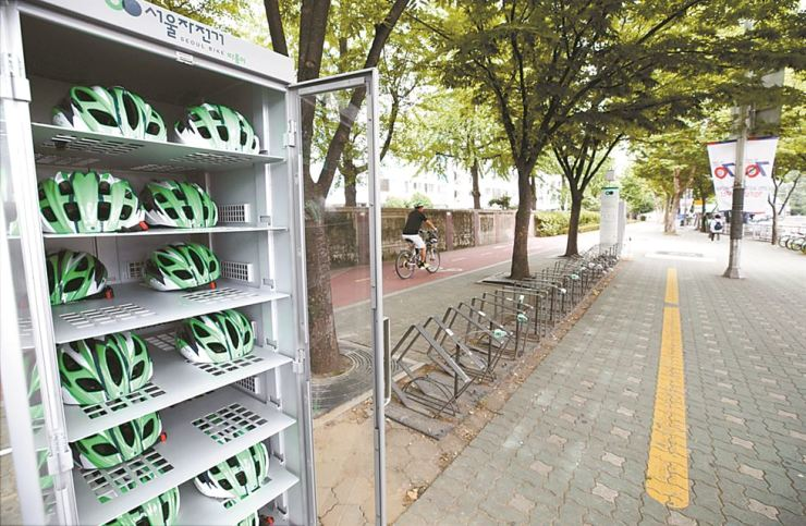Helmets are stored while bicycles are all being used at a bike-sharing station on Yeouido, southern Seoul. The Seoul Metropolitan Government is currently test-operating a free helmet rental service in the area but not many people use the helmets. / Yonhap