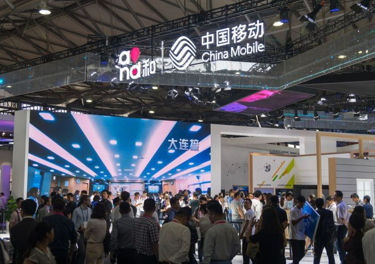 People gather at the China Mobile stand during the Mobile World Conference in Shanghai on June 27. AFP-Yonhap