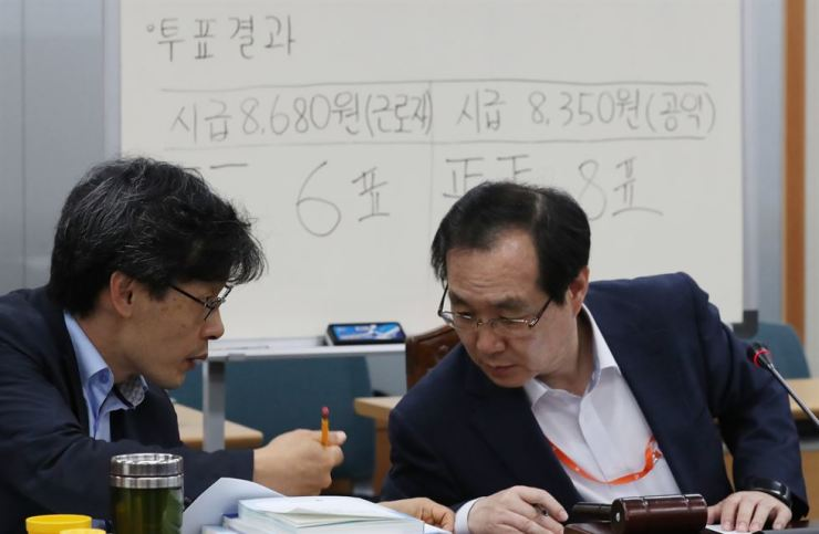 Chairman of the Minimum Wage Council Ryu Jang-soo, right, and the council's Vice-Chairman Kim Sung-ho share words during a press conference at the employment and labor ministry's office in Seoul Government Complex, July 14, 2018. Yonhap
