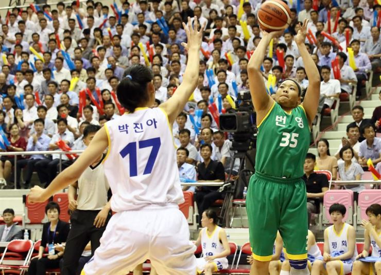 Basketball players in mixed North and South Korean teams compete in a game at the Ryugyong Chung Ju-yung Gymnasium in Pyongyang, Wednesday. / Pyongyang Joint Press Corps