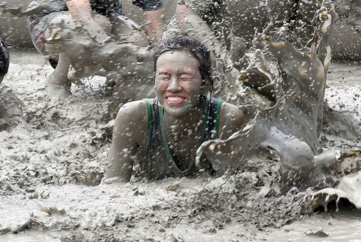 A woman closes her eyes as she dives into a mud pool. Yonhap