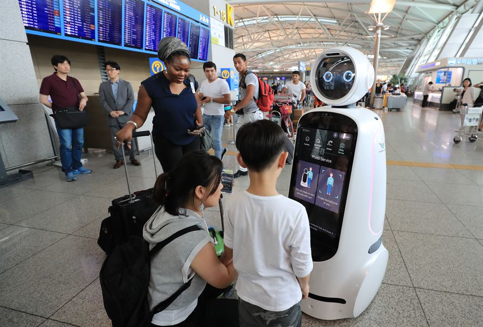 Two guide robots on a trial run at Incheon International Airport's Terminal 1, Wednesday. The airport will put 14 of the robots to work from July 21. / Yonhap