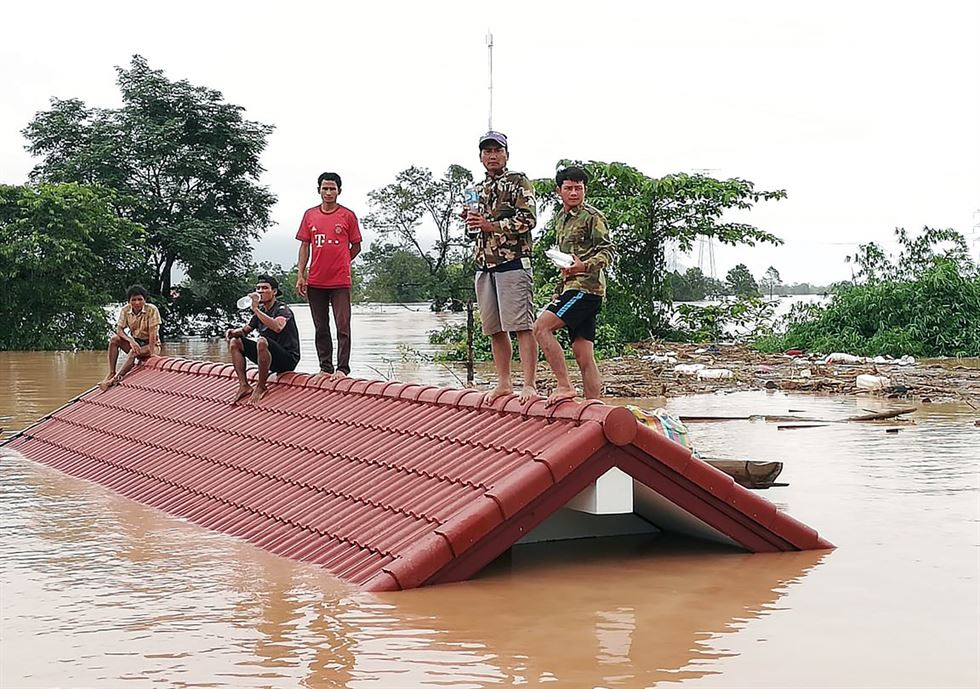 Lao villagers are stranded on a roof of a house after they evacuated floodwaters after the Xe Pian Xe Nam Noy dam collapsed in a village near Attapeu province, Laos, 24 July 2018. / EPA