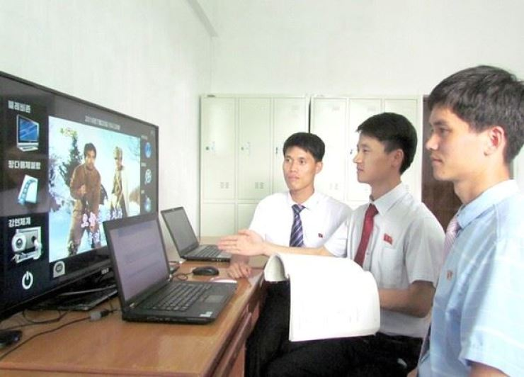 Scientists at Kim Il Sung University look at a TV screen. From DPRK Today