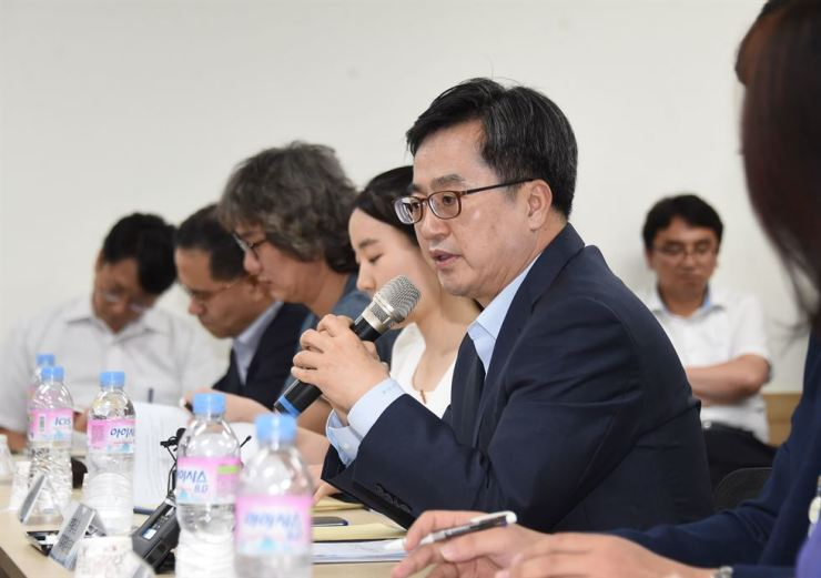 Finance Minister Kim Dong-yeon speaks into a microphone about the government's plan to boost the social safety net at a job training center in Seoul on Aug. 16. Courtesy of the Ministry of Economy and Finance