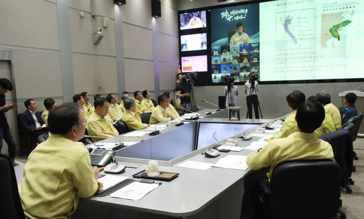Kim Boo-kyum, head of the Ministry of the Interior and Safety, is briefed at the Central Government Complex in Seoul, Friday, about Typhoon Yagi's trajectory and the ongoing heat wave. / Yonhap