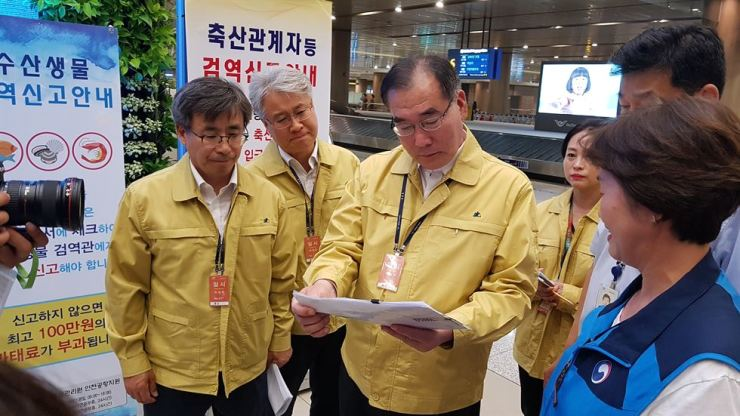 Agriculture Minister Lee Gae-ho, center, inspects Incheon International Airport's border quarantine measures, Saturday, in the wake of the nation's detection of the African swine fever virus gene. / Yonhap