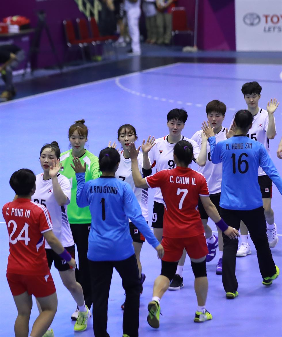 South Korean women's handball head coach Lee Kye-chung, left, speaks with a North Korean coach before the start of an inter-Korean match held at GOR Popki Cibubur in Jakarta, Tuesday. Yonhap