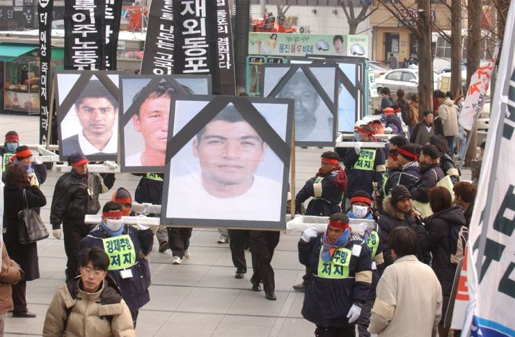 Migrant workers in Korea and supporters of their human rights parade in Jongno-gu, Seoul, in December 2003, bearing photos of migrant workers who died during a crackdown on illegal migrants due for deportation. Protesters demanded no more forced deportations and that migrant workers who have been killed be remembered on International Migrants Day on Dec. 18. Korea Times file