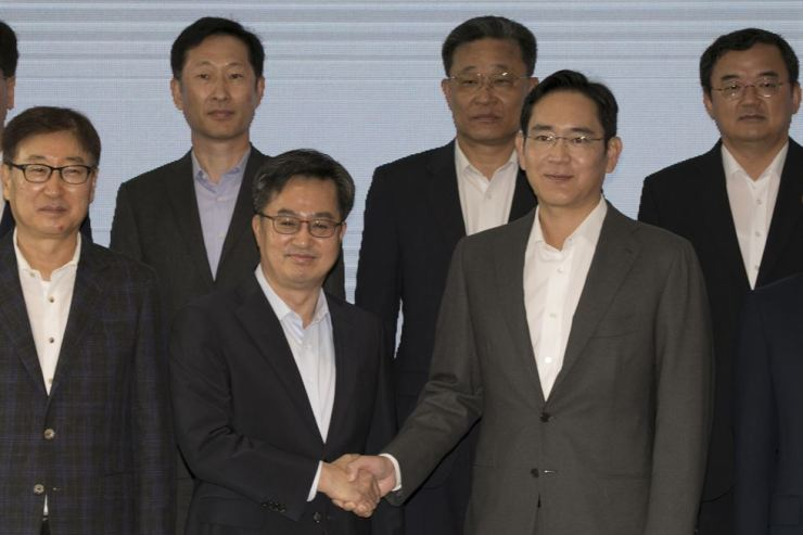 Finance Minister Kim Dong-yeon, second from left, shakes hands with Samsung Electronics Vice Chairman Lee Jae-yong ahead of their meeting at the company's semiconductor plant in Pyeongtaek, Gyeonggi Province, Monday. Yonhap