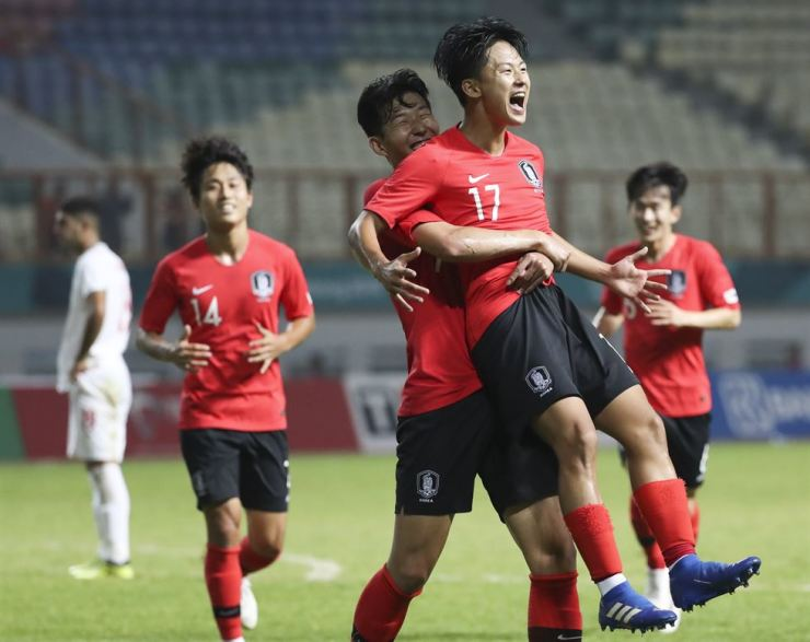 South Korea's Son Heung-min, center, lifts Lee Seung-woo, second from right, celebrating Lee's goal against Iran during the men's football round of 16 match at the 18th Asian Games at Wibawa Mutkit Stadium in Chikarang, Indonesia, Thursday. Yonhap