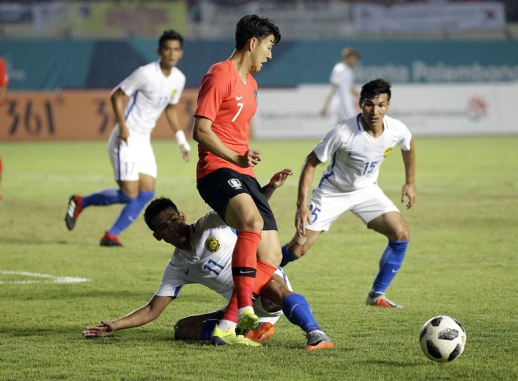 South Korea's Son Heung-min, center, battles for the ball with Malaysia's Muhammad Safari Rasid, on ground, and Mohd Rizal Ghazali during their football game at the at Si Jalak Harupat Stadium in Bandung, Indonesia. AP-Yonhap